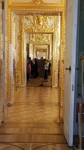 Looking down the hall at the succession of golden opulence.
