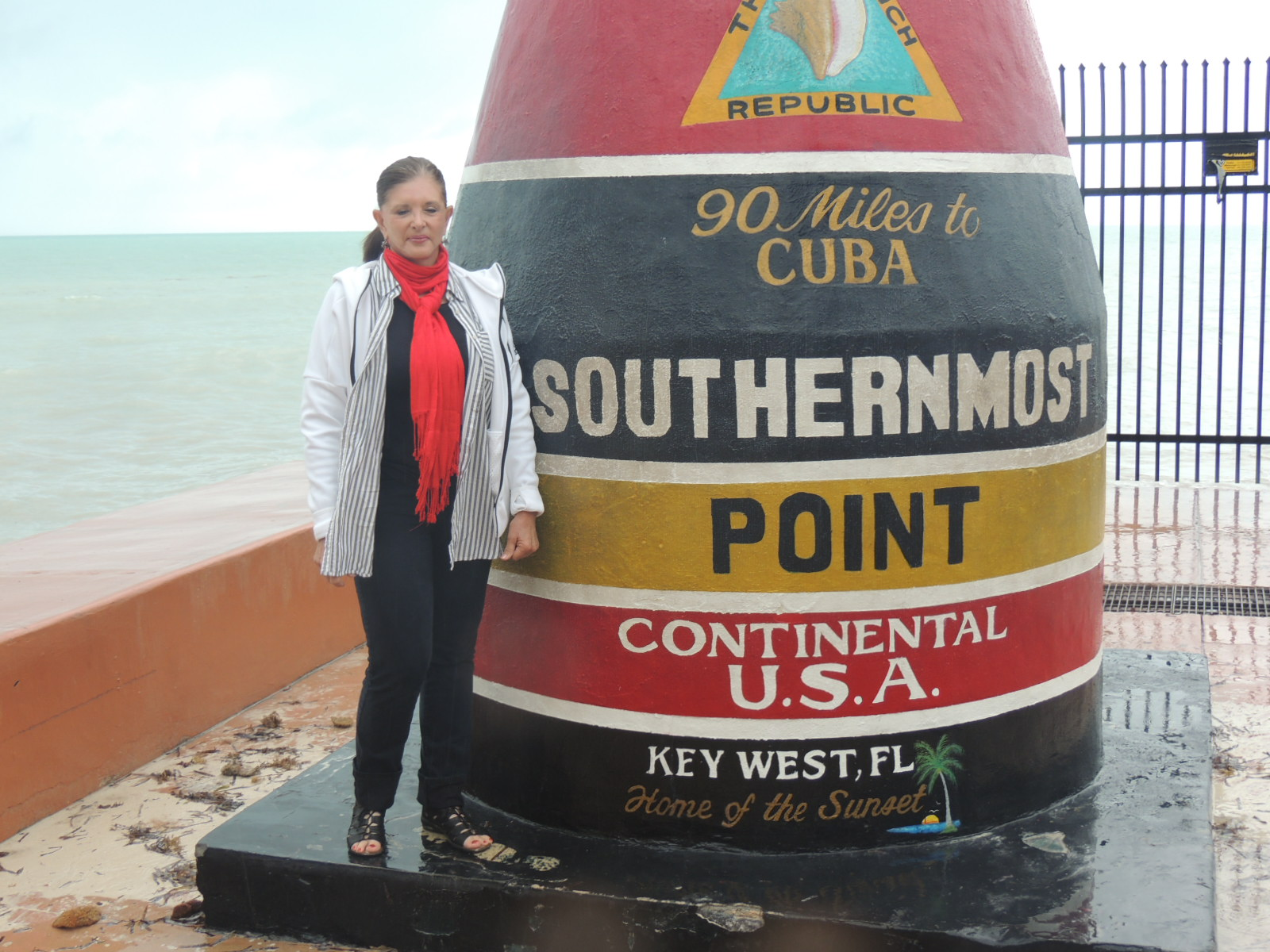 Annie standing in front of the Southernmost Point in the Continental USA.