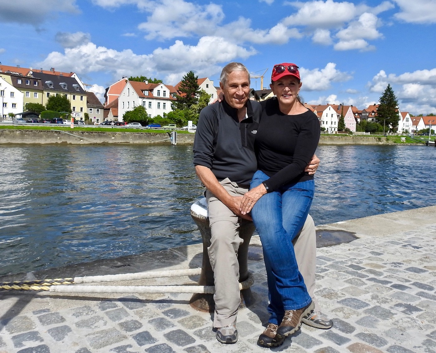 Annie and Bruce in front of Bavarian houses in Regensburg. The Danube flows in the background.