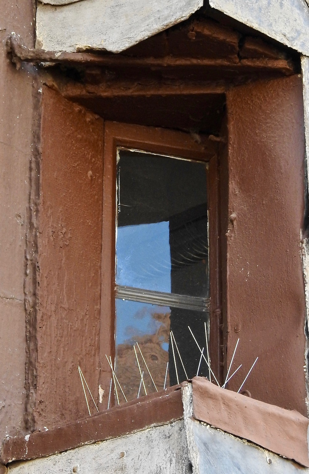 A narrow window used for spying on neighbors without being seen.
