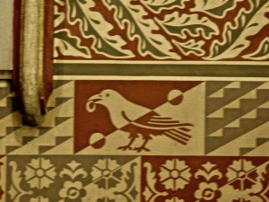 Raven with gold ring motif along the wall beneath the coat-of-arms.