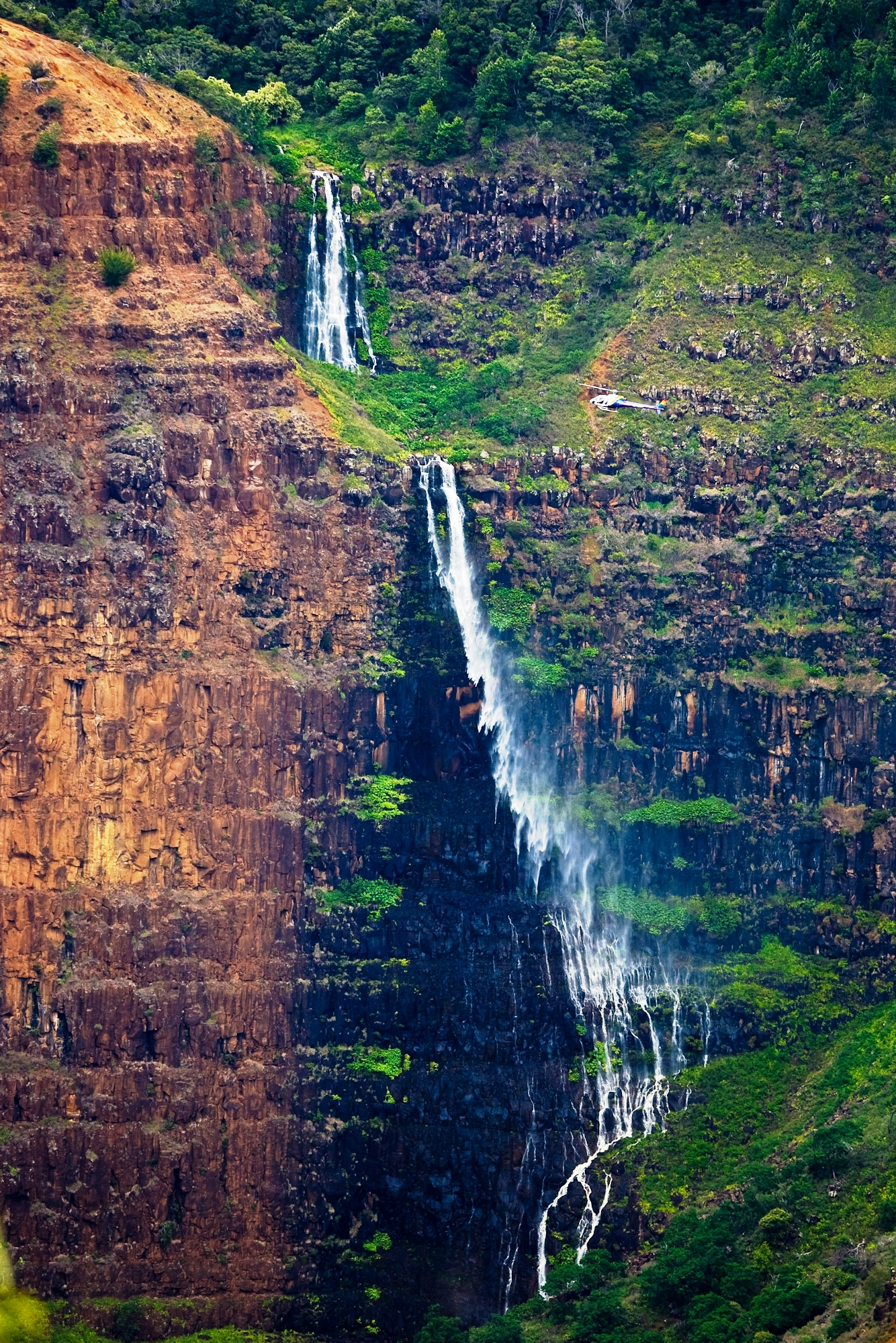 Helicopter viewing a waterfall in the Waimea Canyon, nicknamed the Grand Canyon of the Pacific