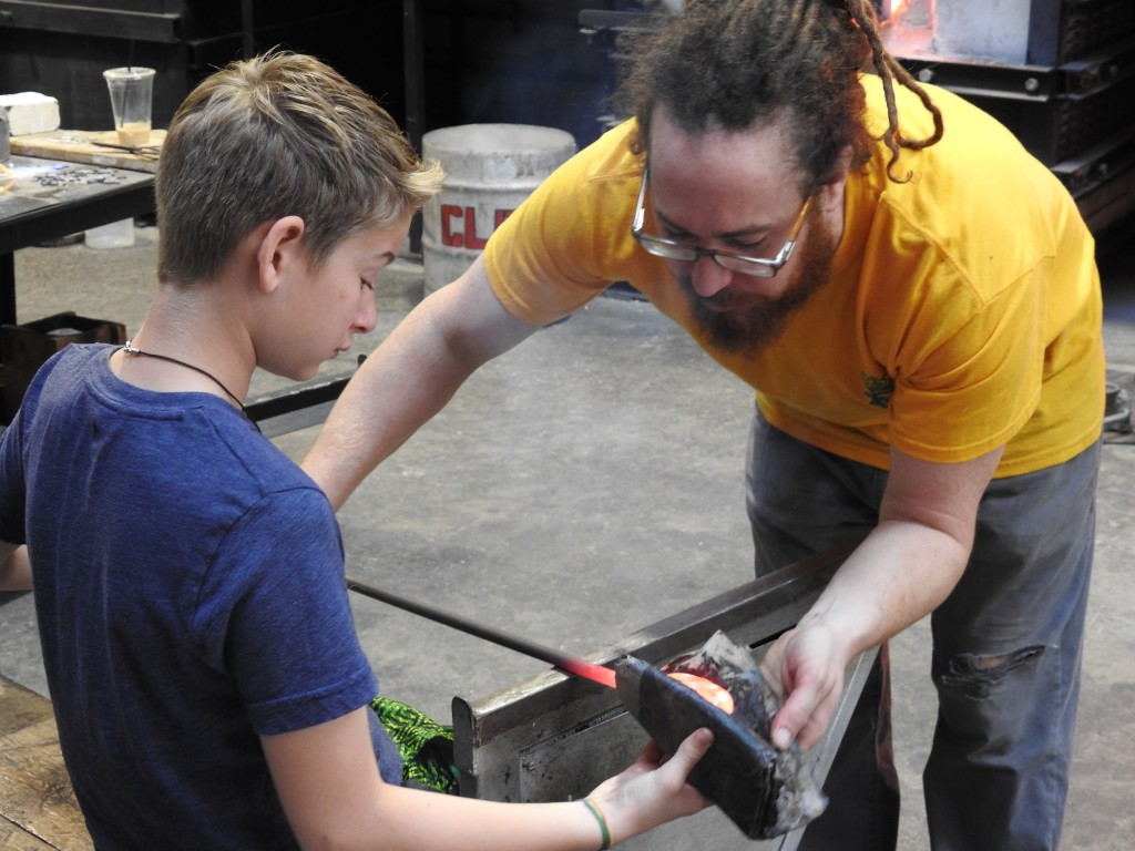 Bodhi and Zach shaping the glass. That's damp newspaper used as a shaping tool.